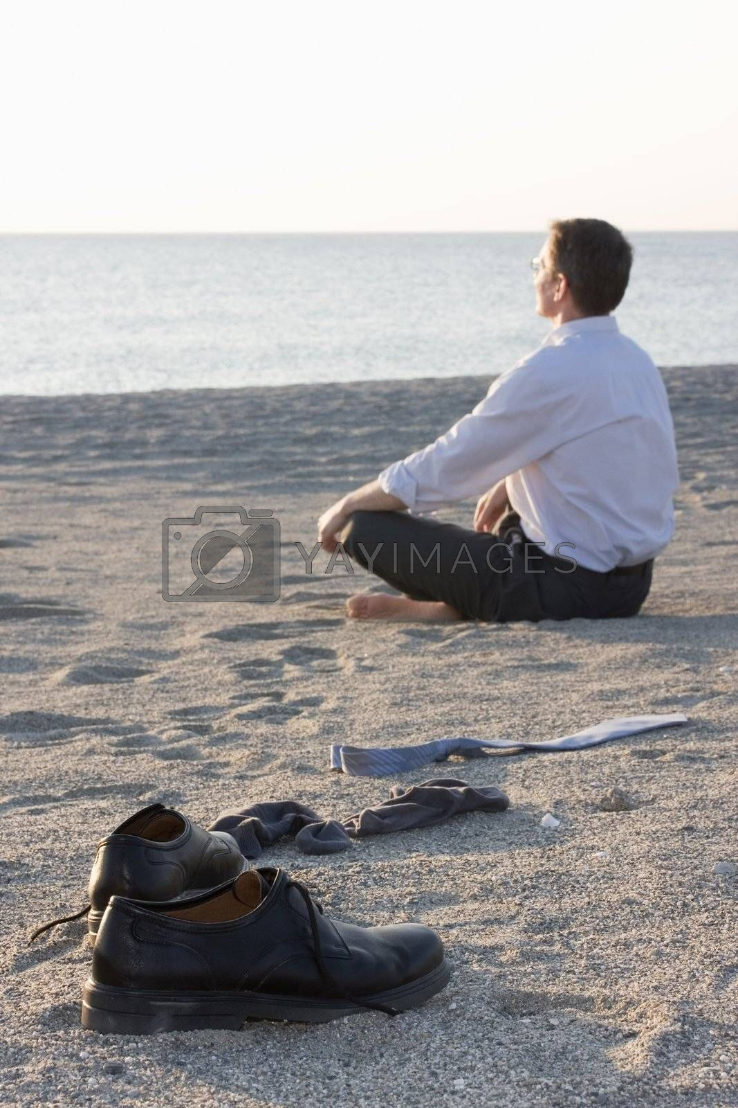 Businessman relaxing on beach - Focus on the shoes in the foreground
