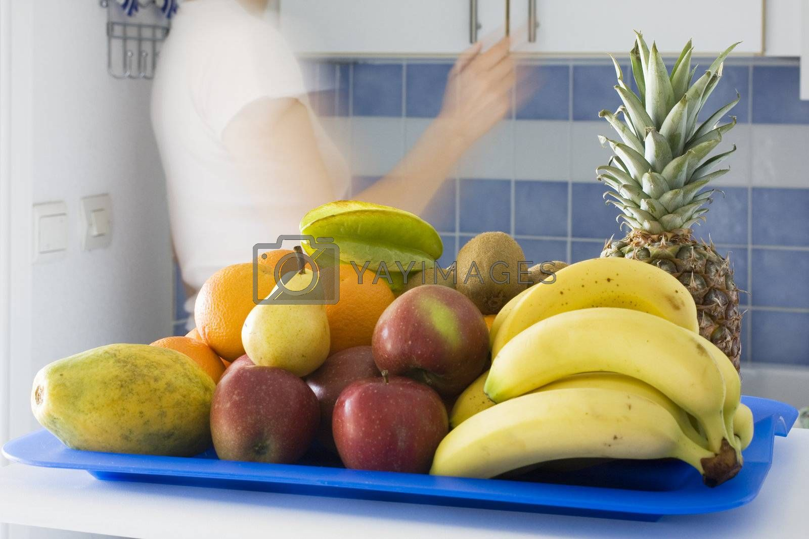 Fruits in a kitchen with blurred moving woman in the background