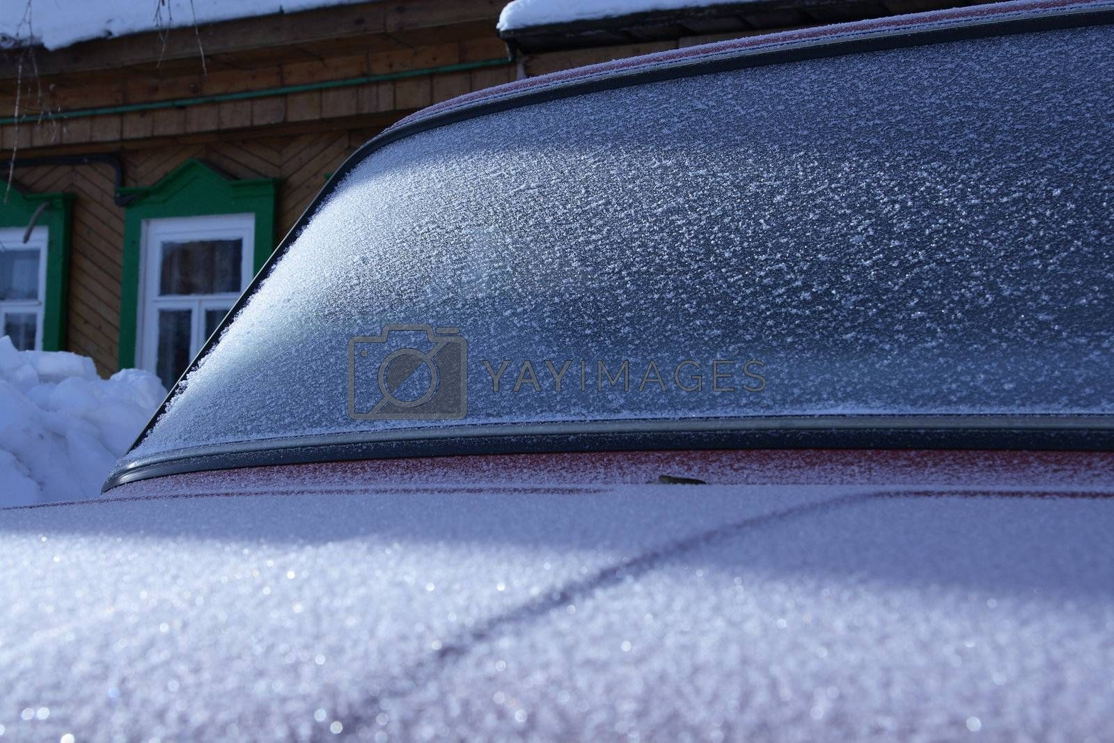 The car covered with frost, against the old wooden house. by mzh25