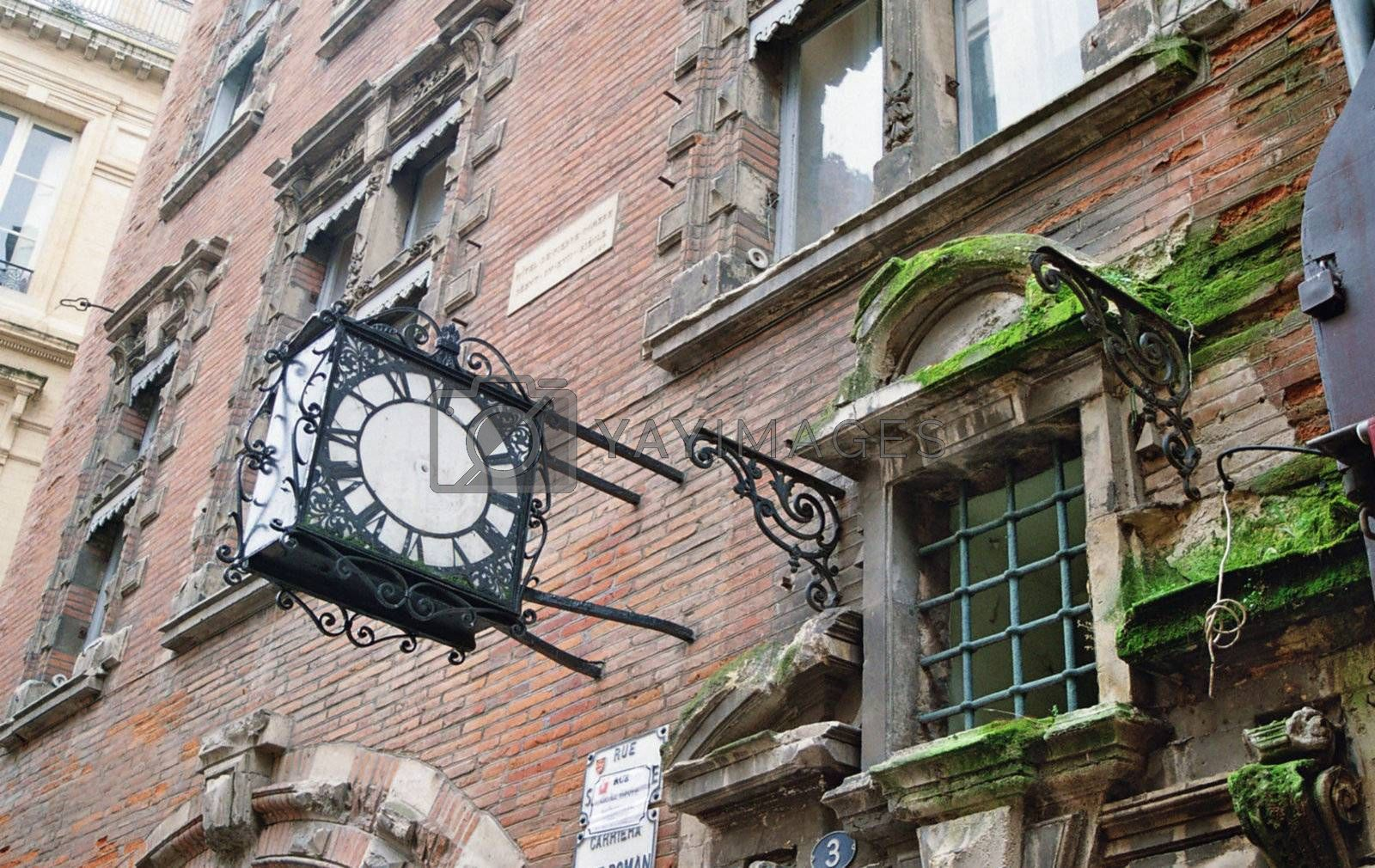 old, pointerless clock and old window in toulouse
