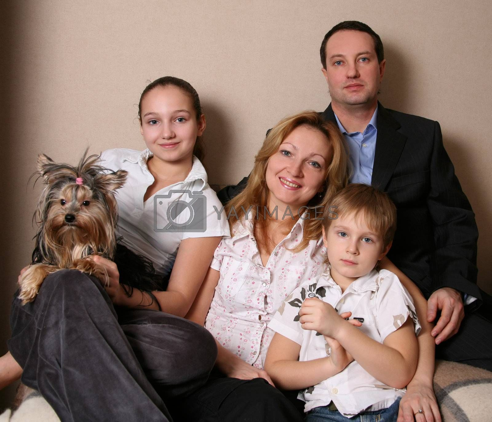Mum, daddy, two children and yorkshire terrier on a sofa
