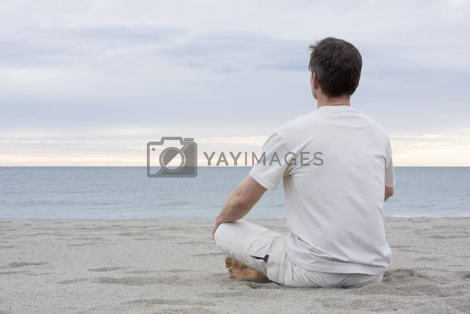Man in white meditating on a beach
