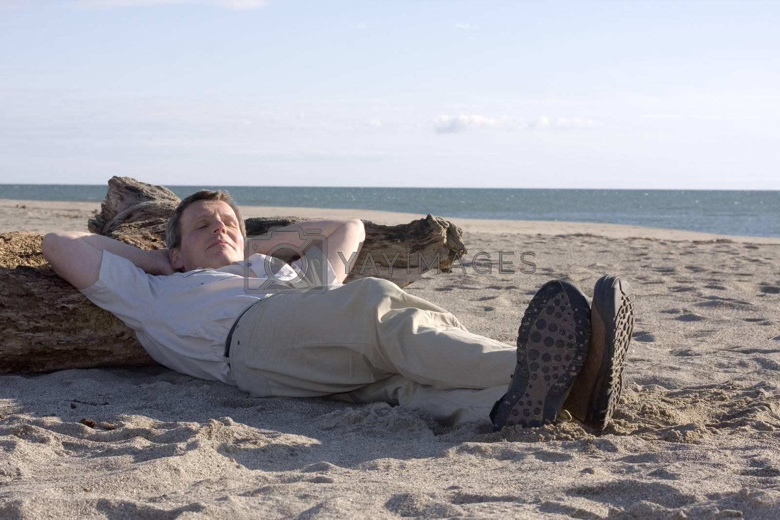 Man sleeping on a beach on a sunny day
