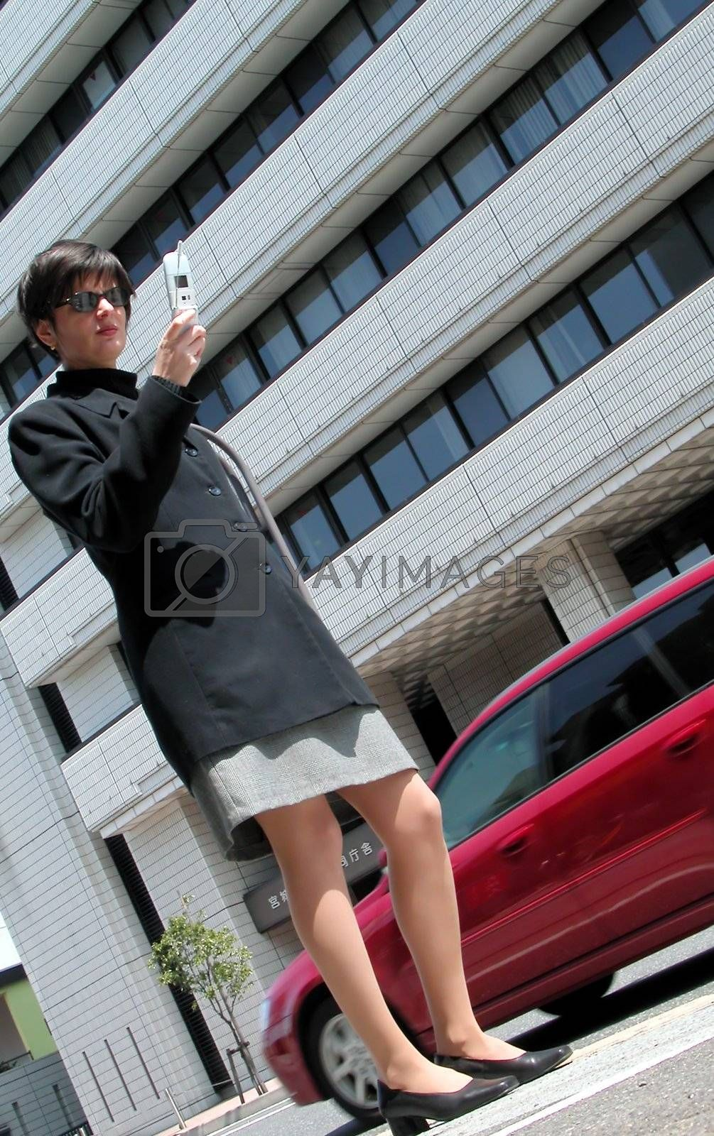 Woman using phone in the street in a big city
