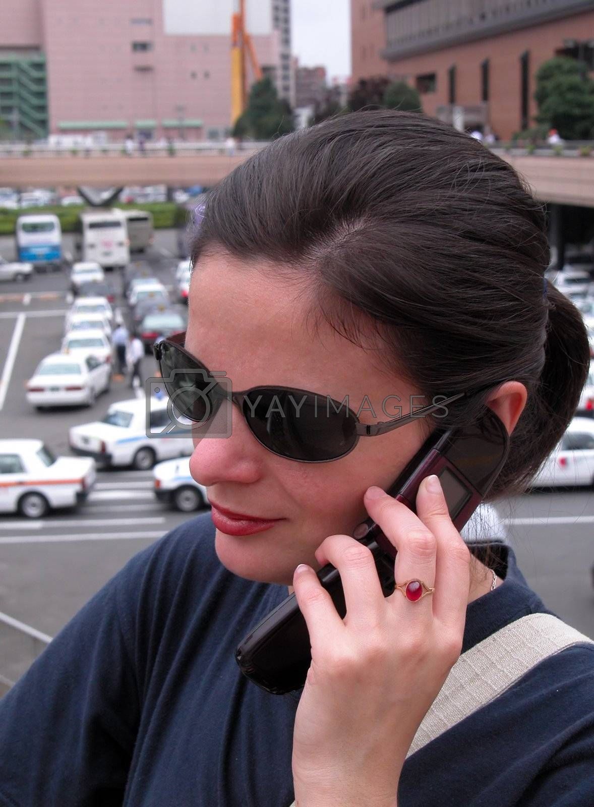 Woman with sunglasses using mobile phone in a big city.