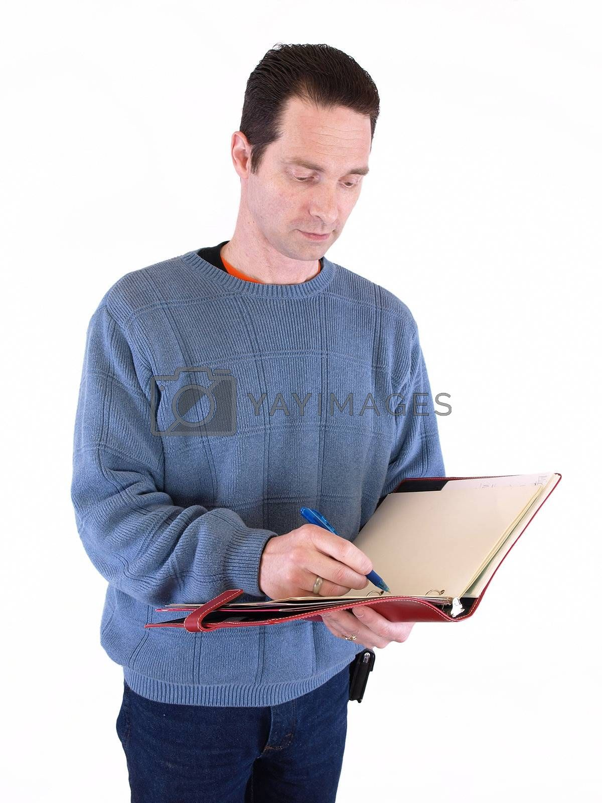 An adult male taking notes in a binder, isolated against a white background.