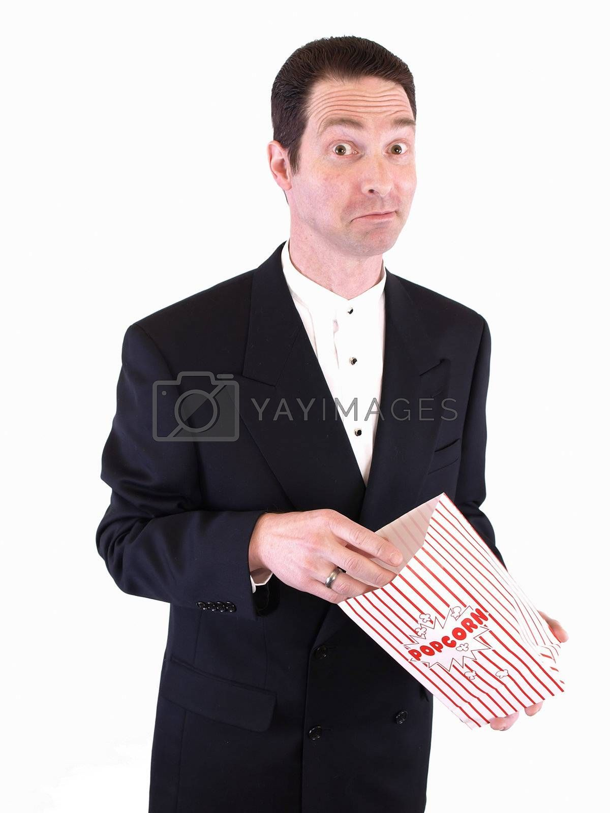 A white male in a suit puts his hand into a popcorn bag. He is chewing on something in his mouth.
