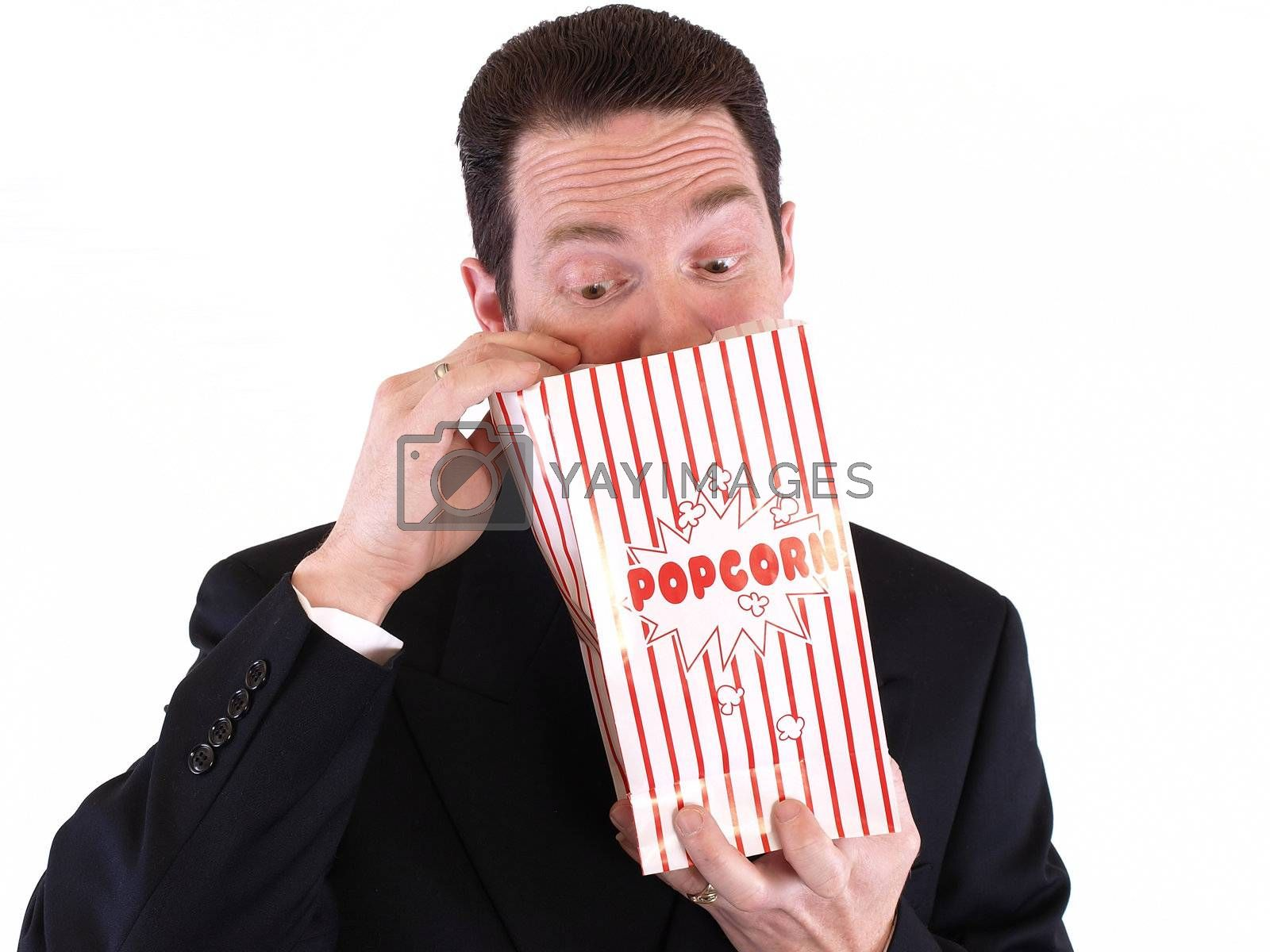 Adult male in a suit holding a popcorn bag and looking in. Isolated on a white background.