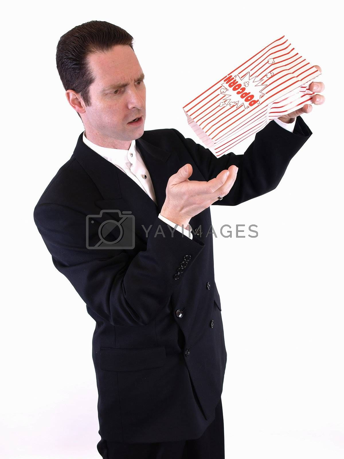 A white male in a suit shakes a bag of popcorn into his hand.  He is frustrated because there is no more.