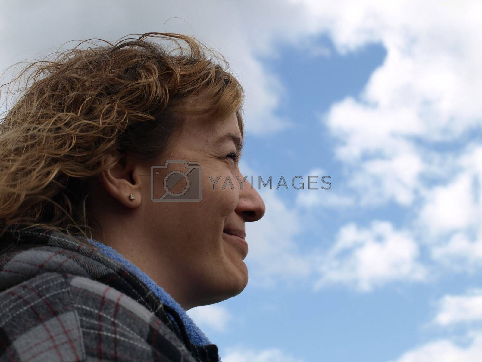 A woman smiles, her back to the gray clouds, looking toward the bright sunny skies.