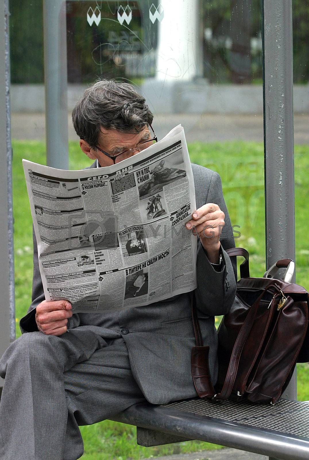 The man reads the newspaper at a bus stop