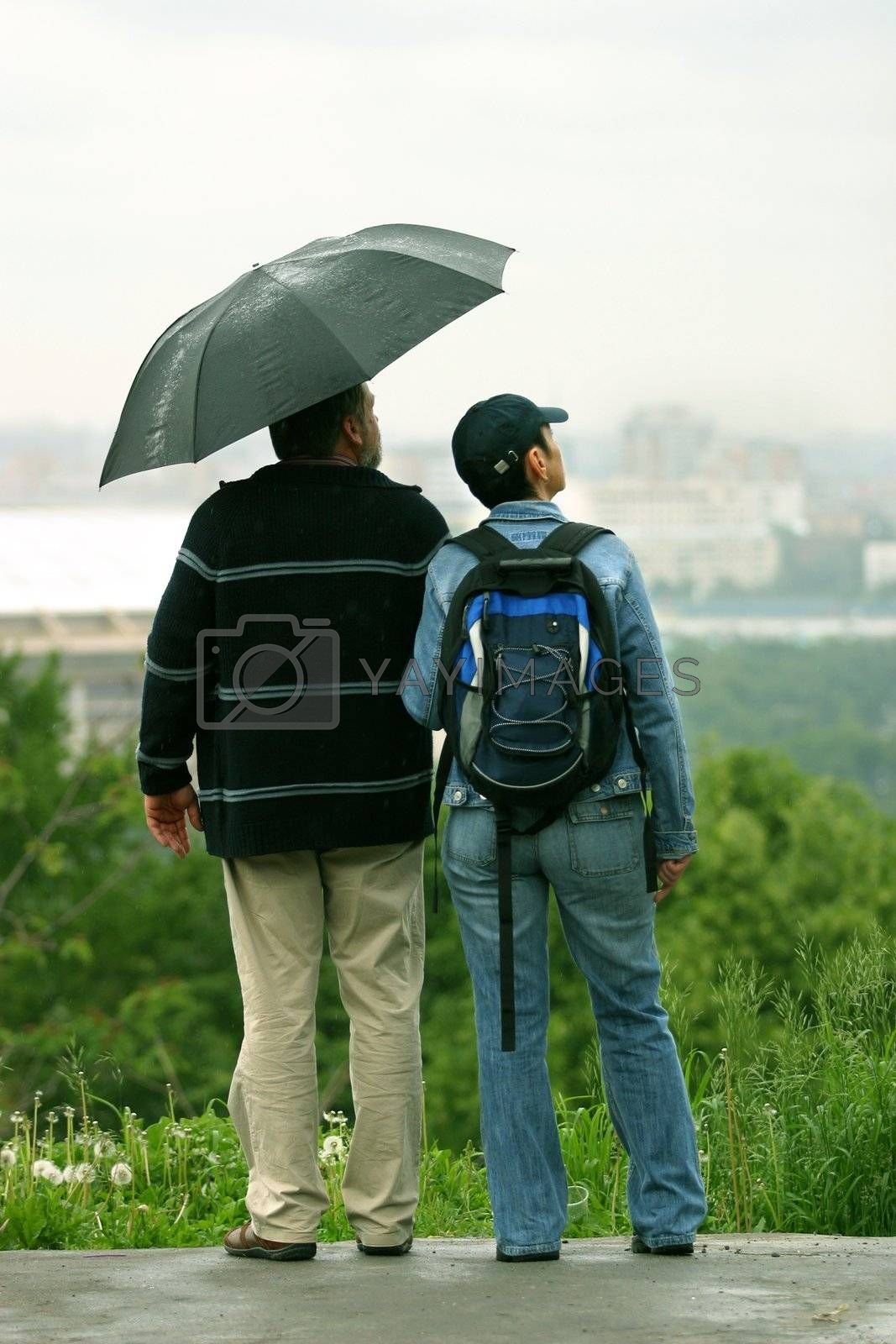The man and the woman under a umbrella