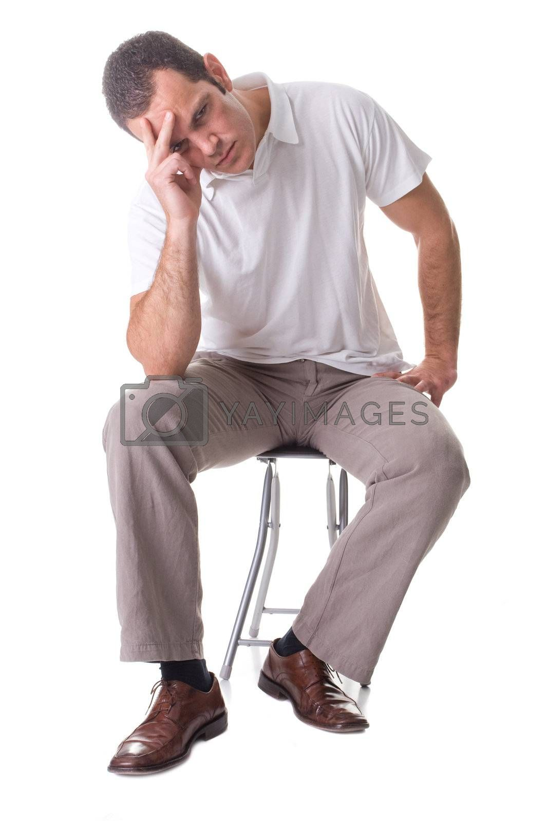 A young man, sitting on a stool, thinking. Isolated on white background.