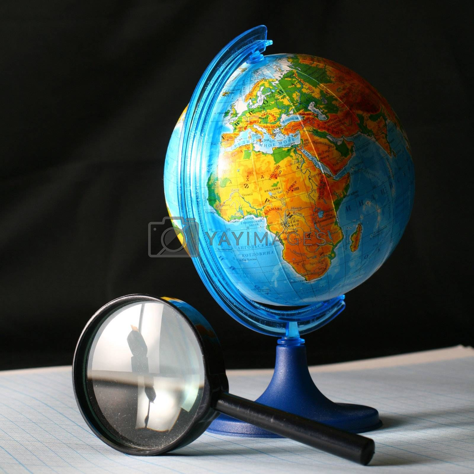 earth globe and magnifier in dark