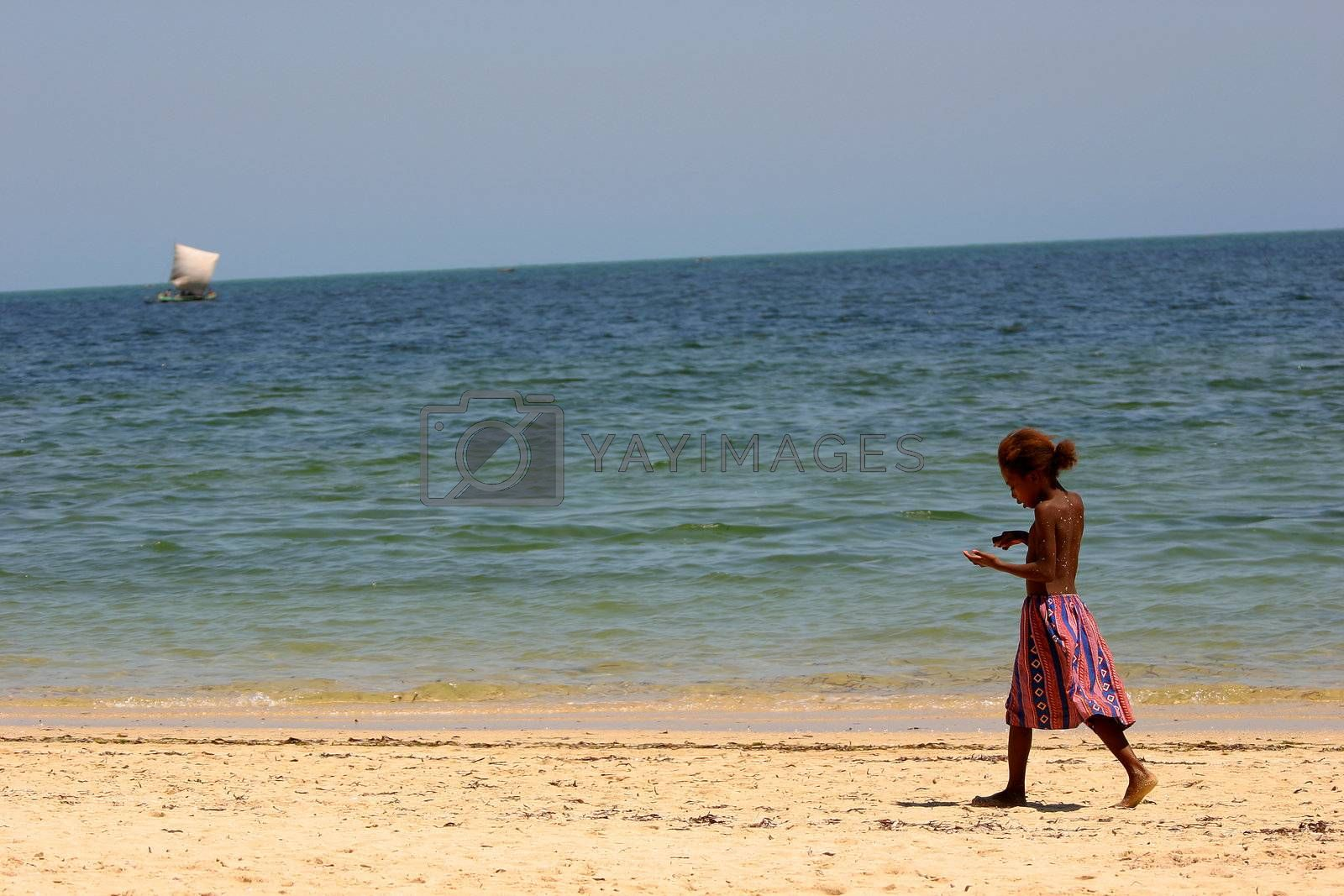 Young girl wandering along the beach at Ifaty