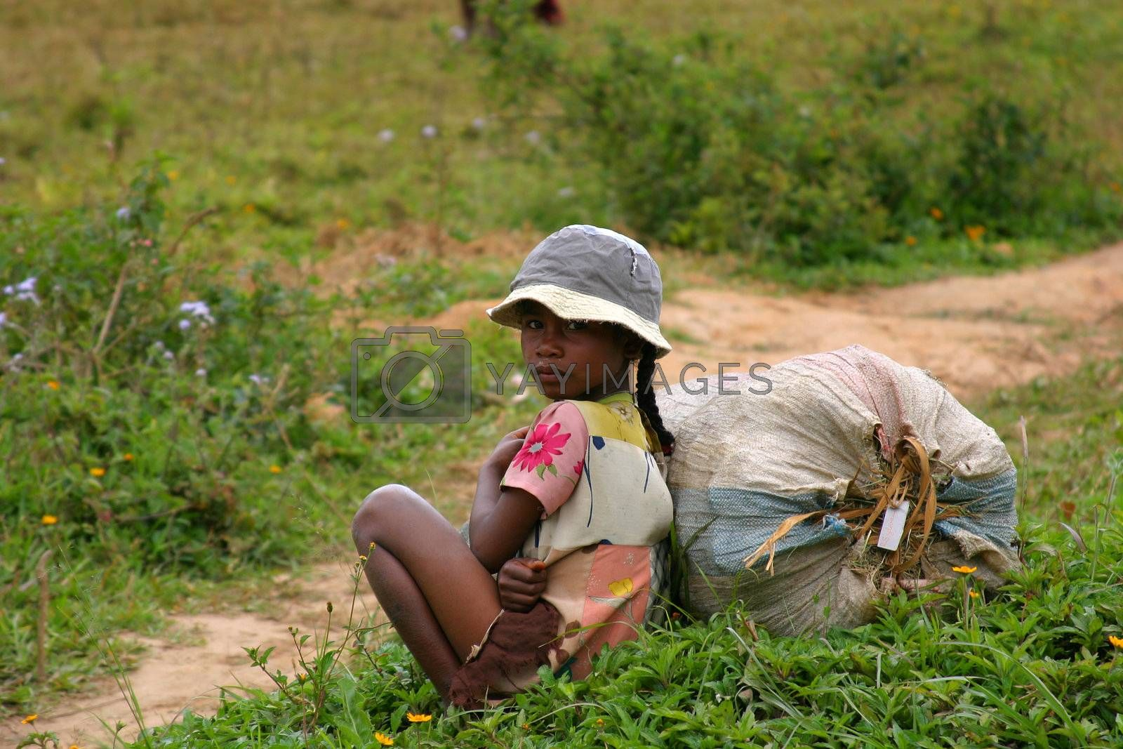 Pretty young girl sitting besides the road in Madagascar
