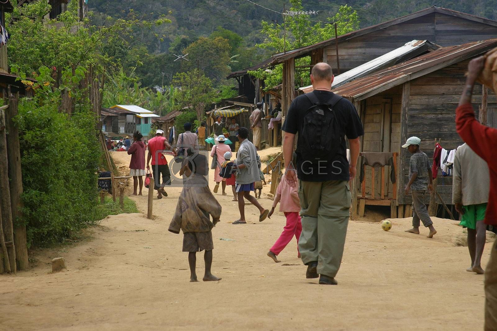 Large tourist man walking among the children in a small town in Madagascar