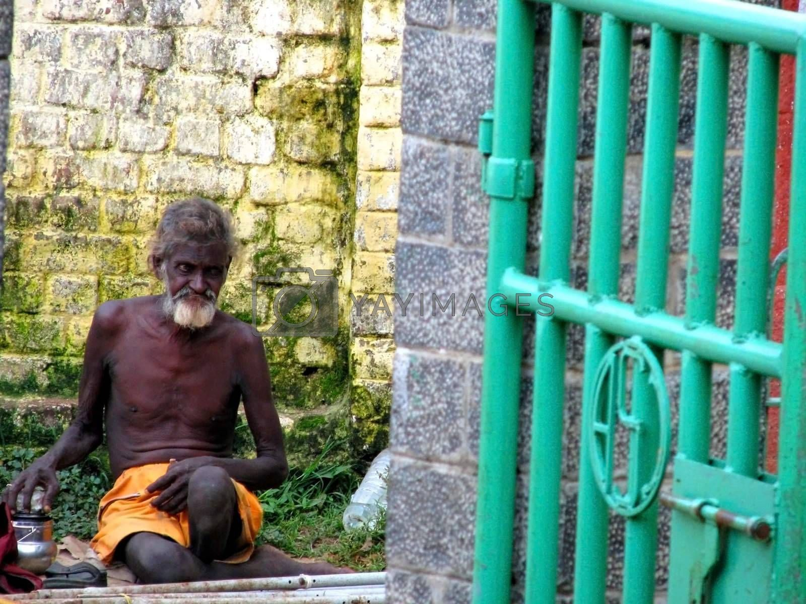 An elderly man in India waits at a gate entry.