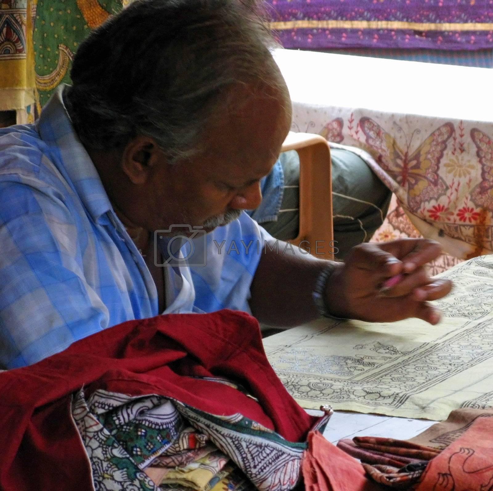 An elderly artist in India creates cloth artwork.