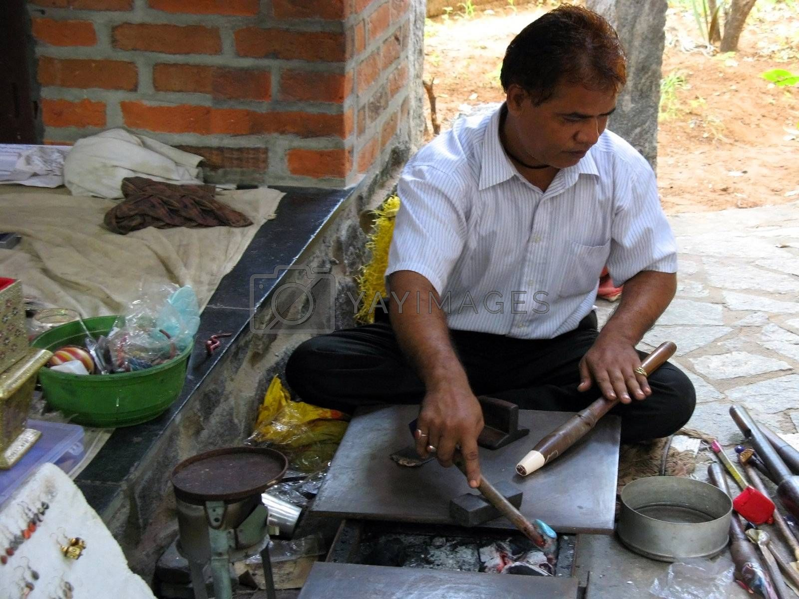 An artist in India creates jewelry.