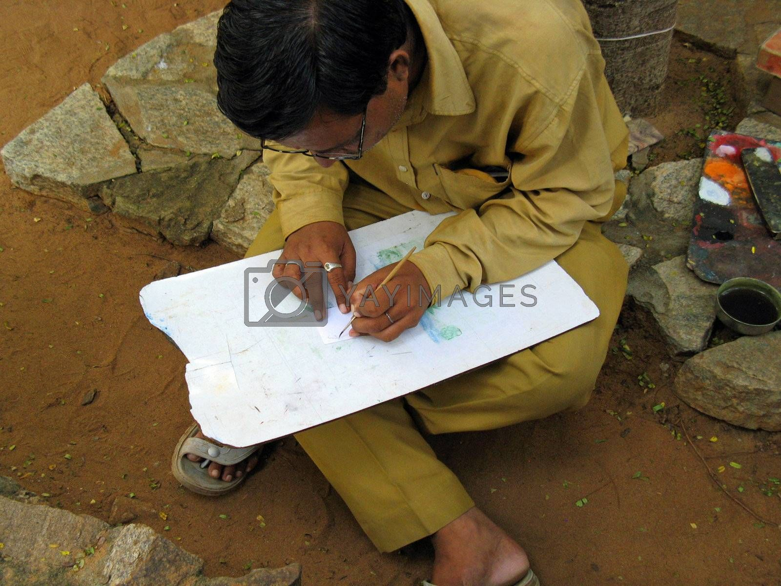 An artist in India creates painted artwork.