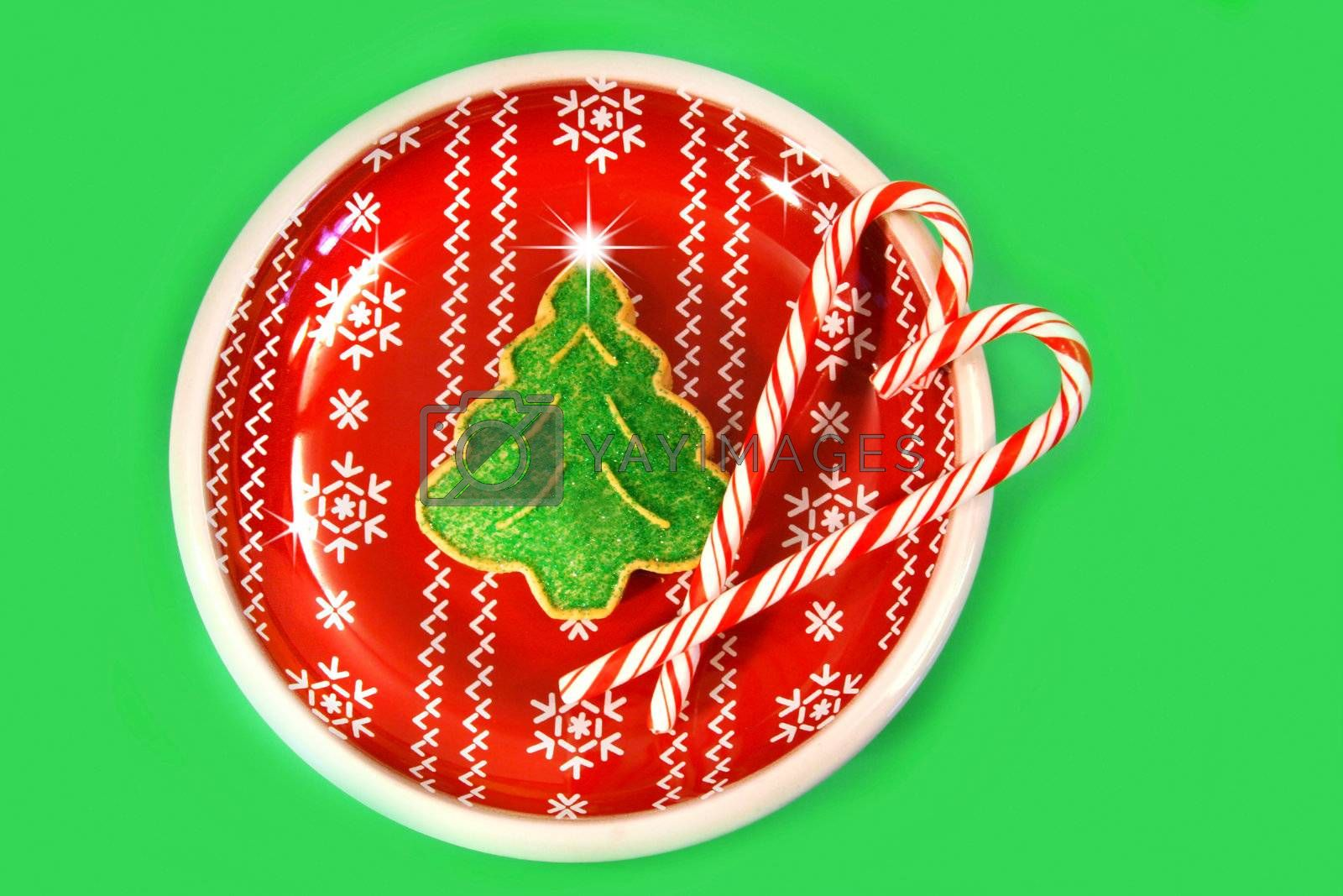 Green christmas tree cookie with candy canes on red plate