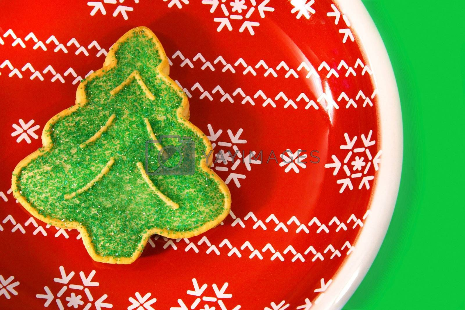 Green christmas tree cookie on a red holiday plate