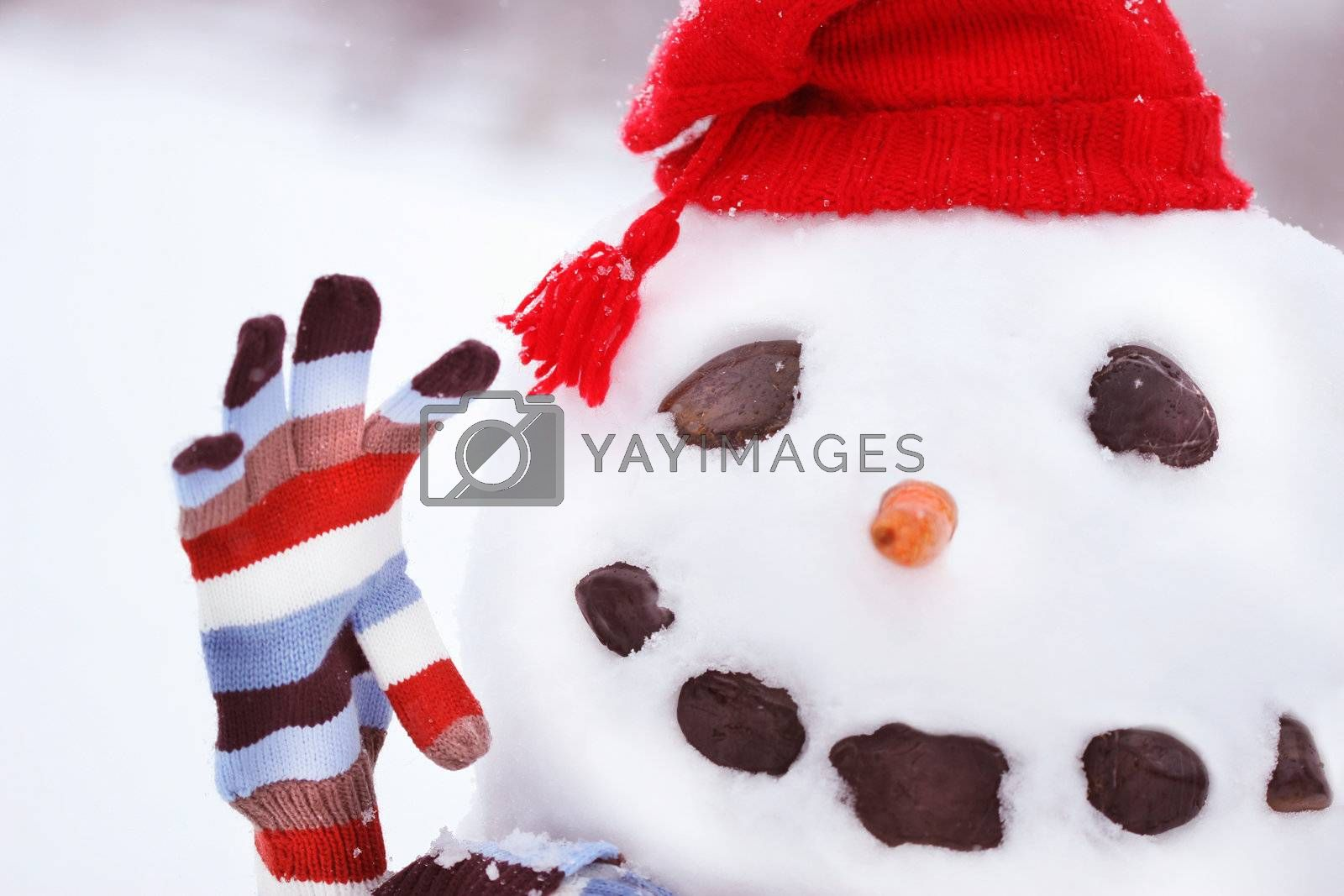 Snowman  in snow with big smile waving