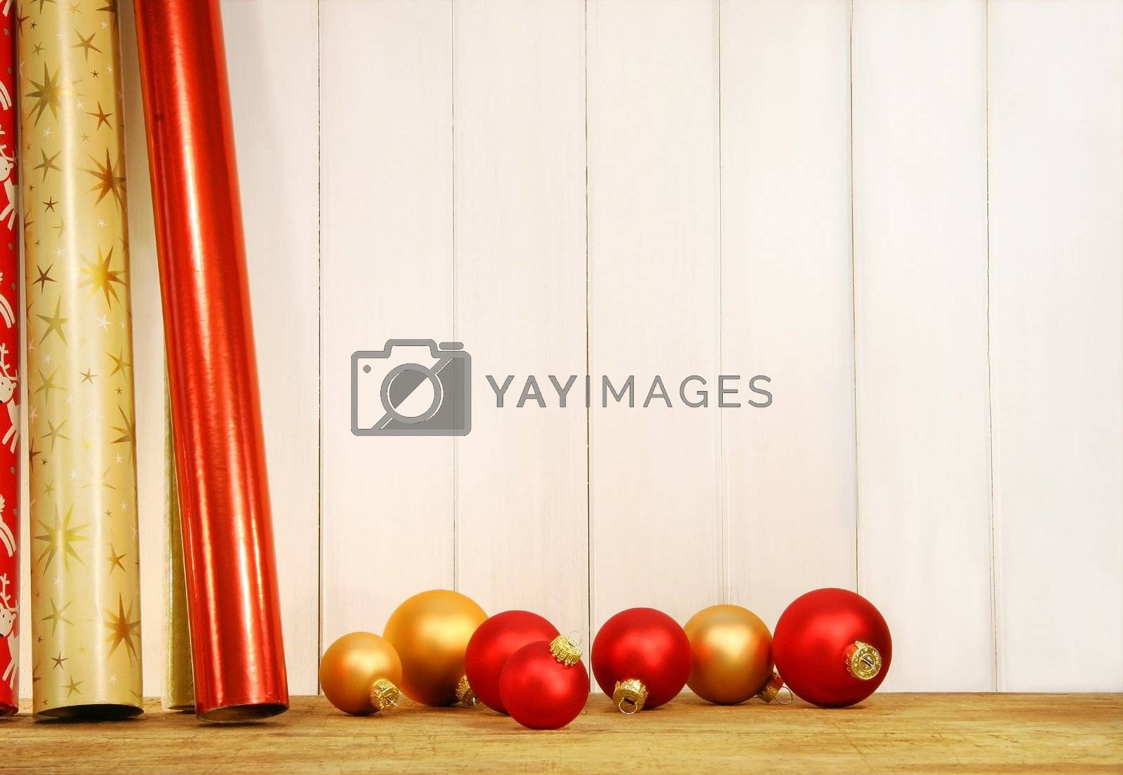 Rolls of holiday wrapping paper against wall with glass balls