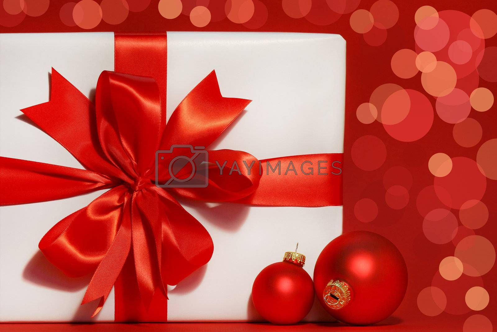 Big red bow on gift with red background and christmas balls