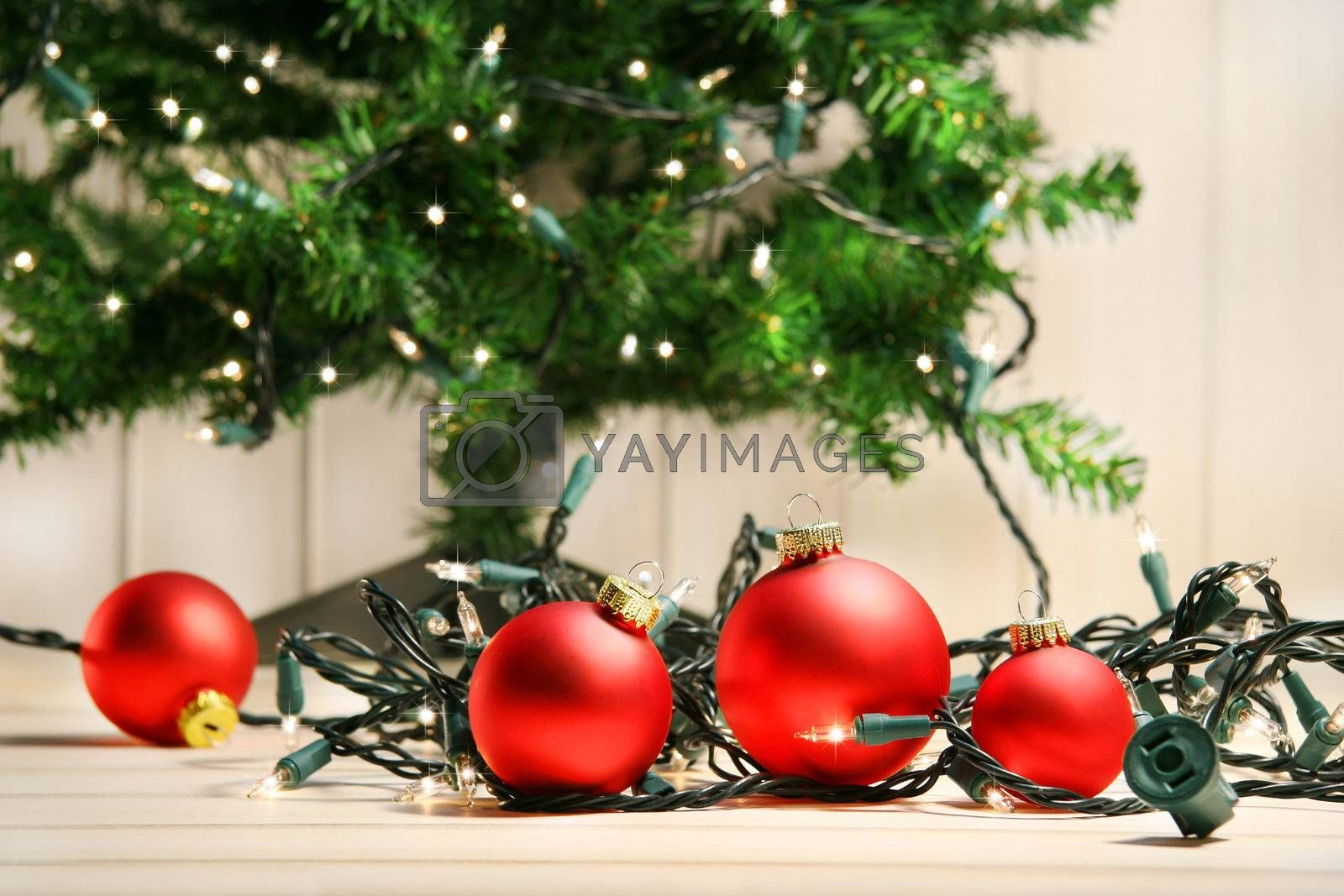 Red glass balls with lights under the christmas tree