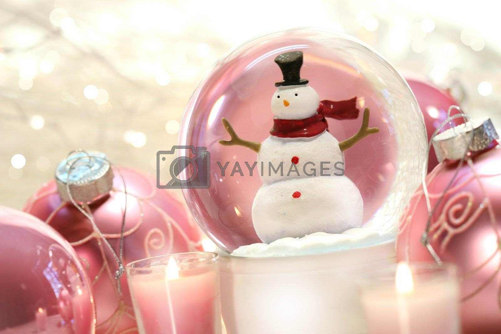 Snow globe with pink christmas balls and white lights in background