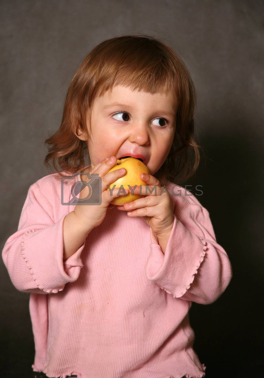 The little girl eats a yellow apple