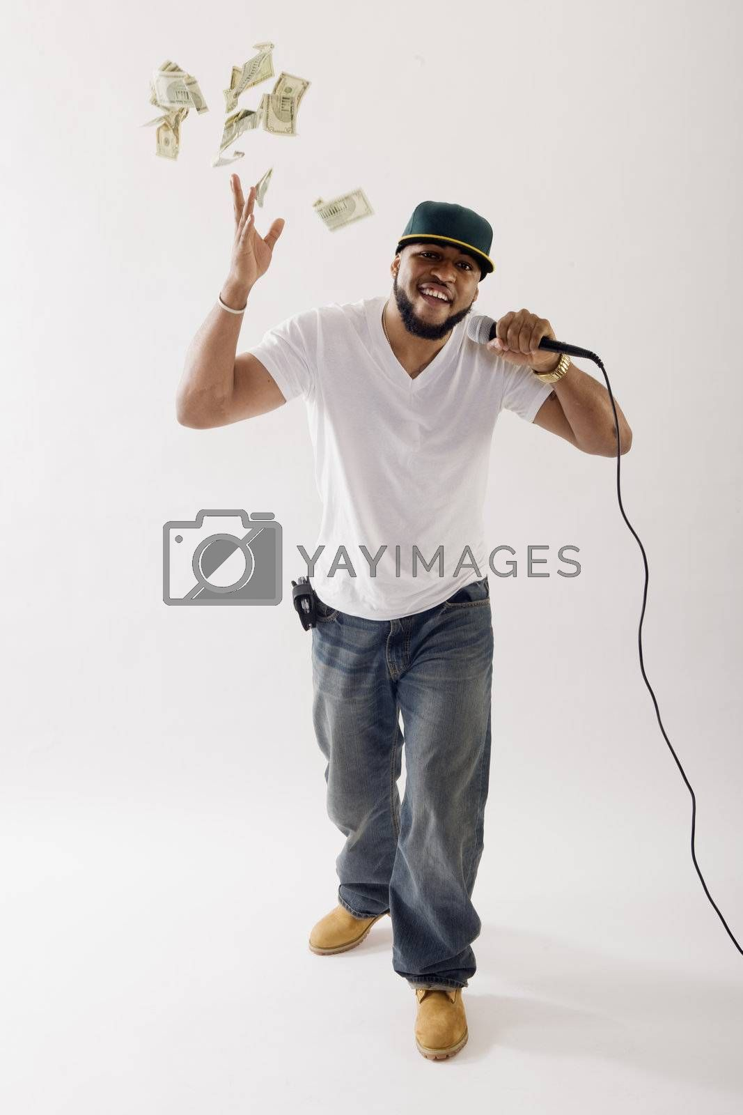 Black vocalist singing into microphone tossing money in the air