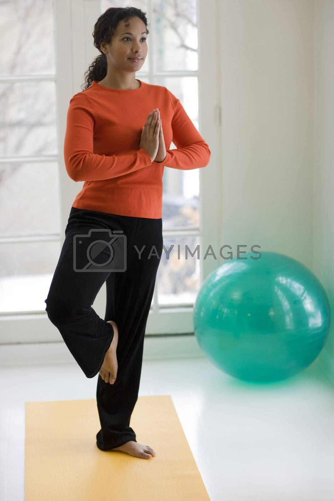 Young African American woman in yoga Tree pose at home