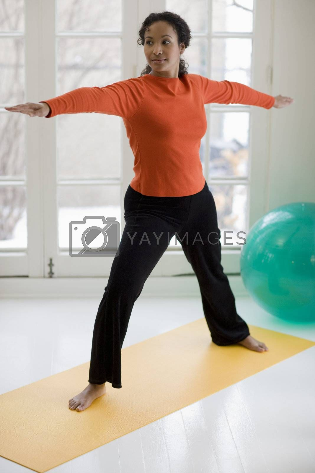 Attractive young African American woman in yoga Warrior pose at home