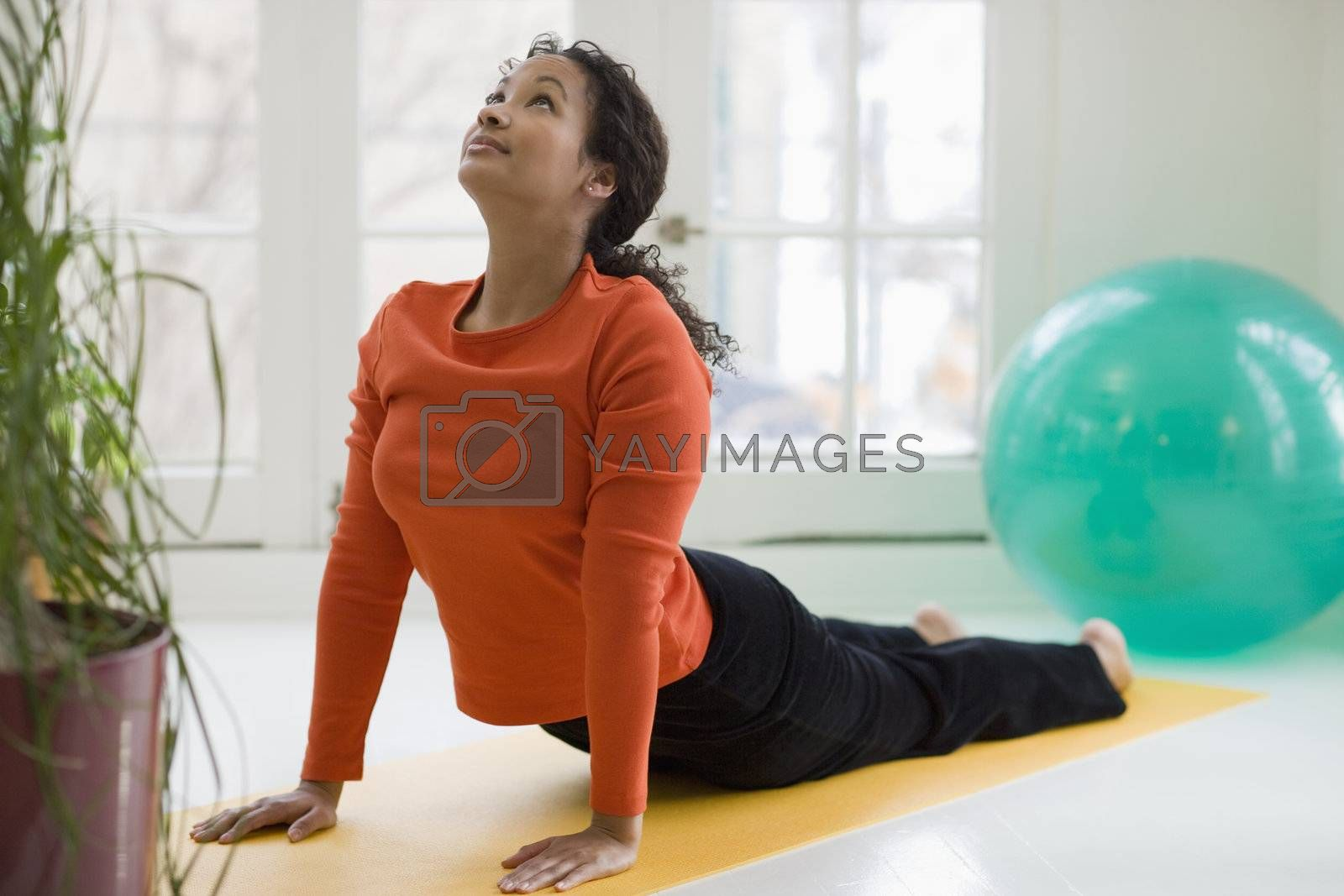 Attractive young African American woman in yoga Cobra pose