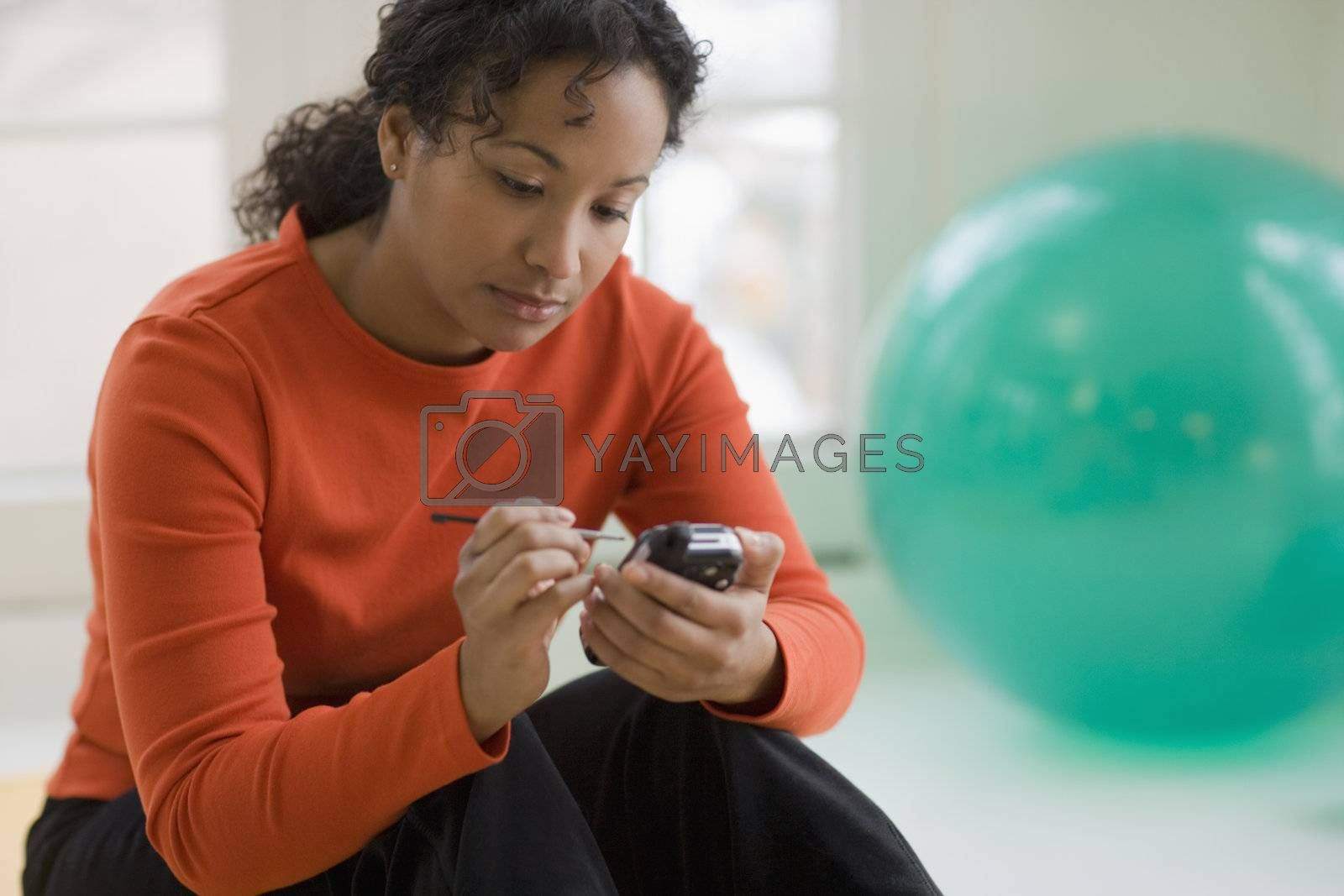 Young African American woman text messaging on cell phone