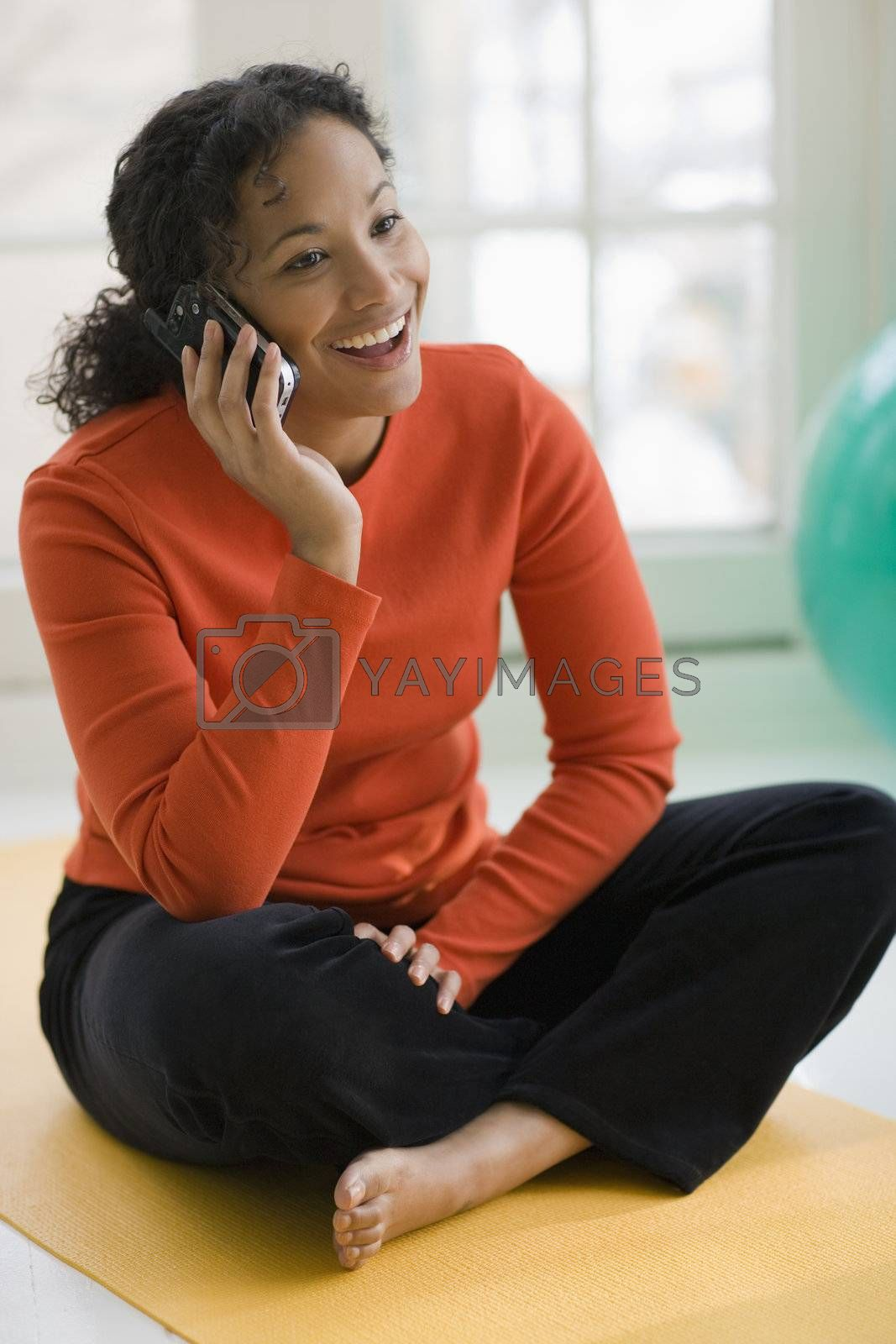 Smiling beautiful African American woman sitting on yoga mat talking on cell phone