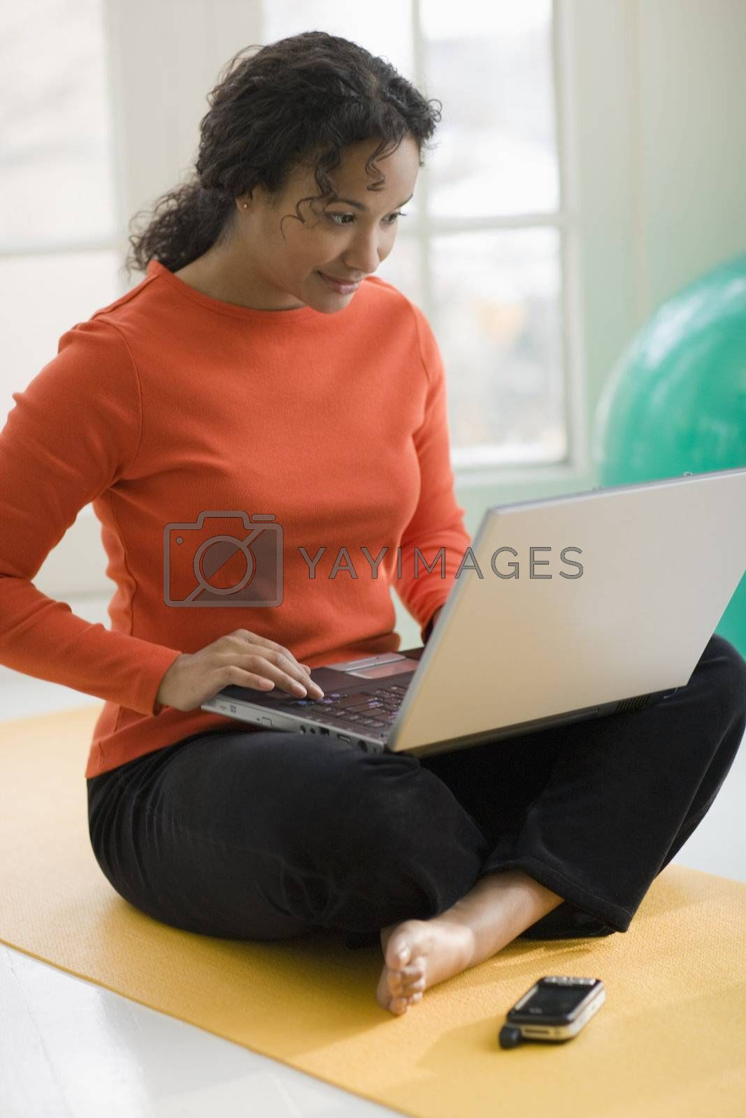 Beautiful young African American woman sitting on yoga mat using her laptop