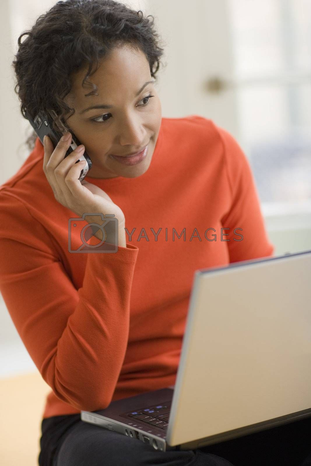 Beautiful young African American woman using cell phone and laptop