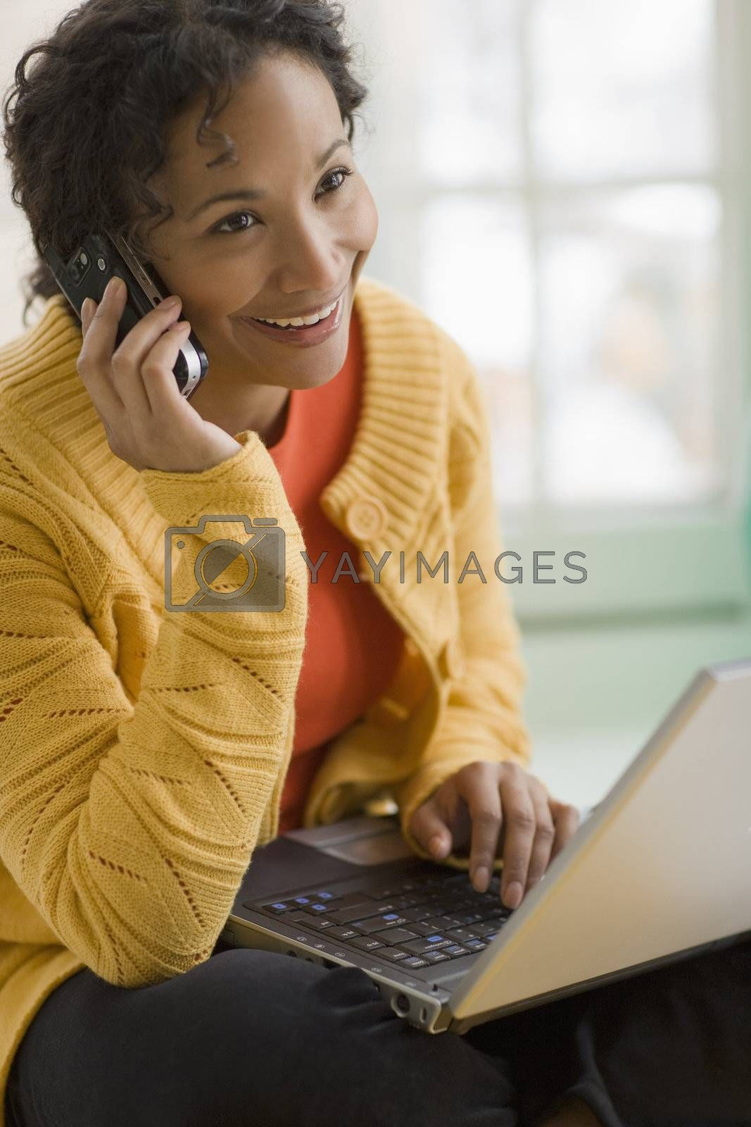 Beautiful young smiling African American woman using cell phone and laptop