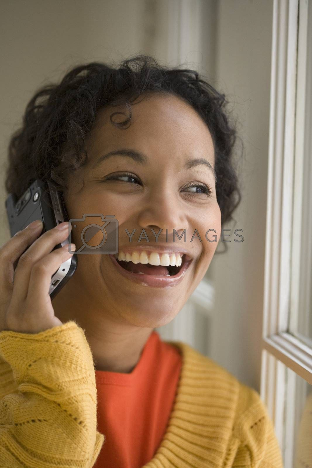 Young beautiful African American woman laughing on cell phone