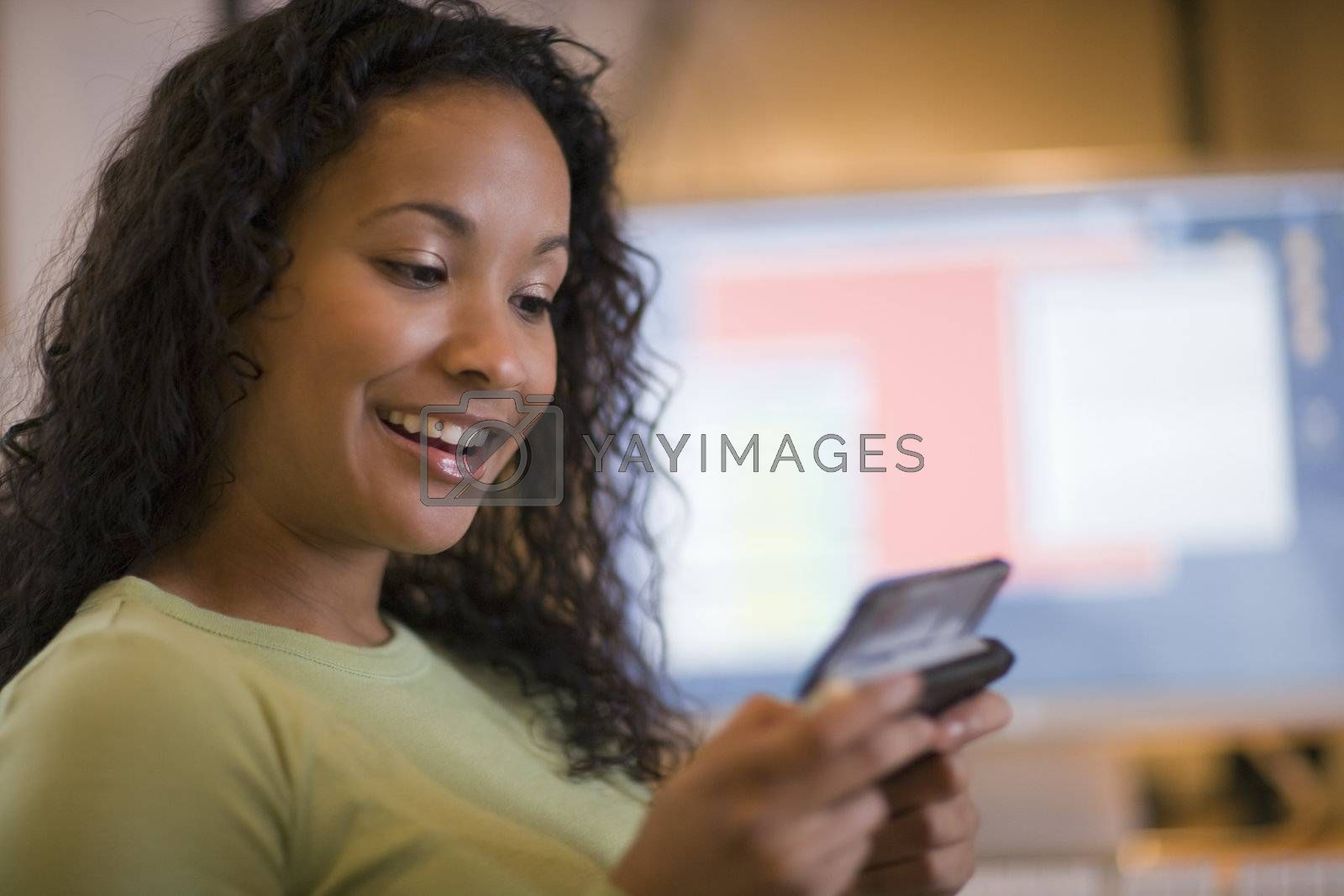 Smiling young African American woman texting on cell phone with computer monitor in the background on desk