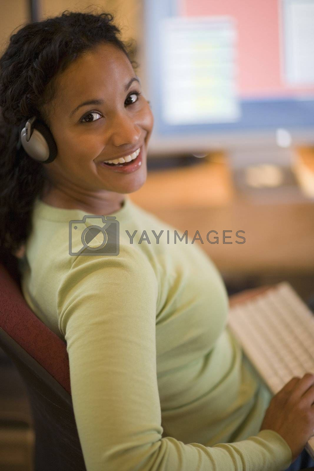 Smiling young African American woman with keyboard in lap and computer on desk