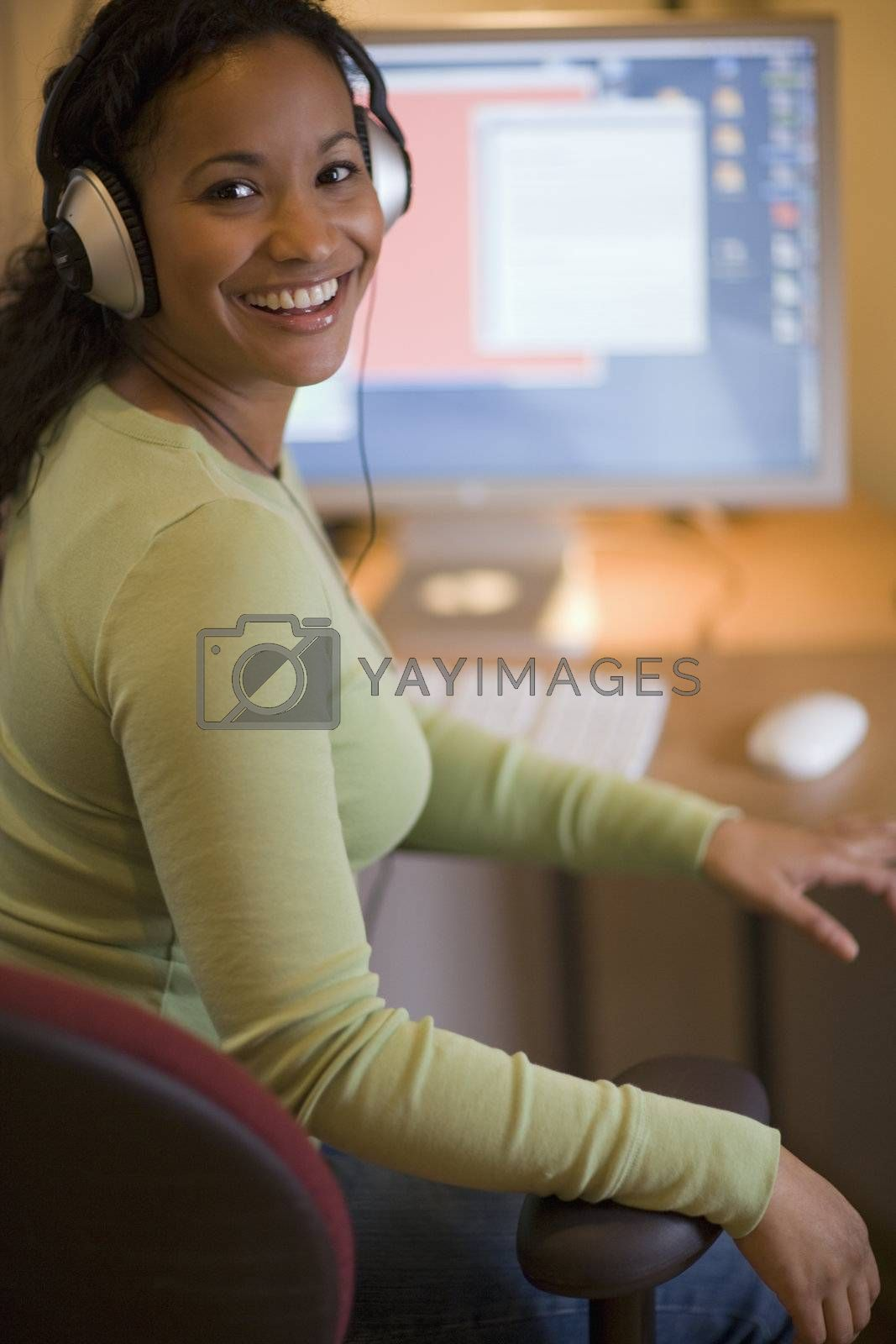 Smiling young African American woman with headphones at desk with computer