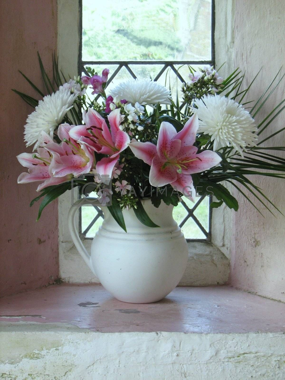 bunch of pink and white flowers standing in a window