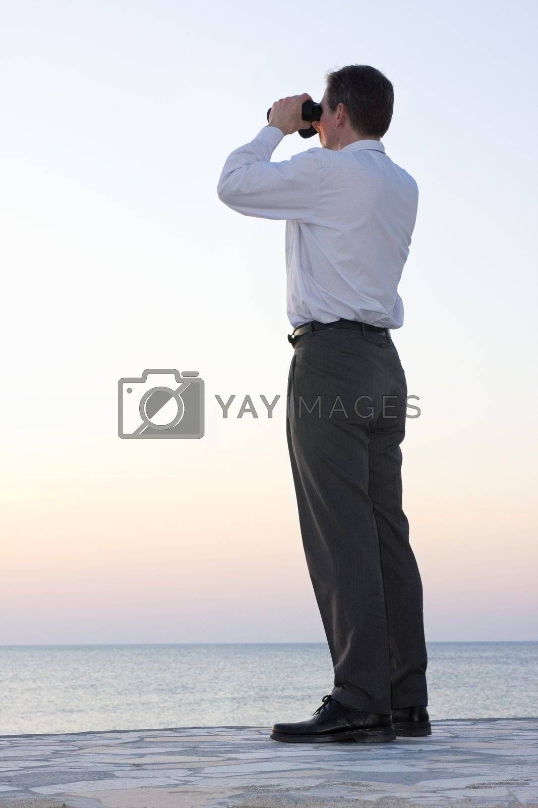 Businessman looking through field glasses at the sea