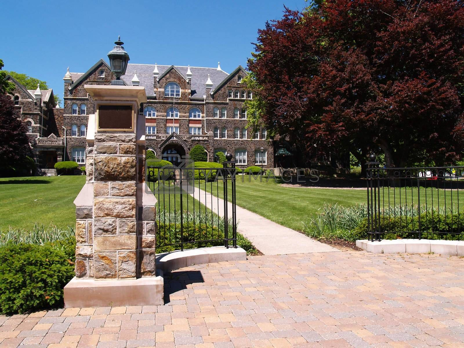 a brick sidewalk and iron gate in front of an old stone college