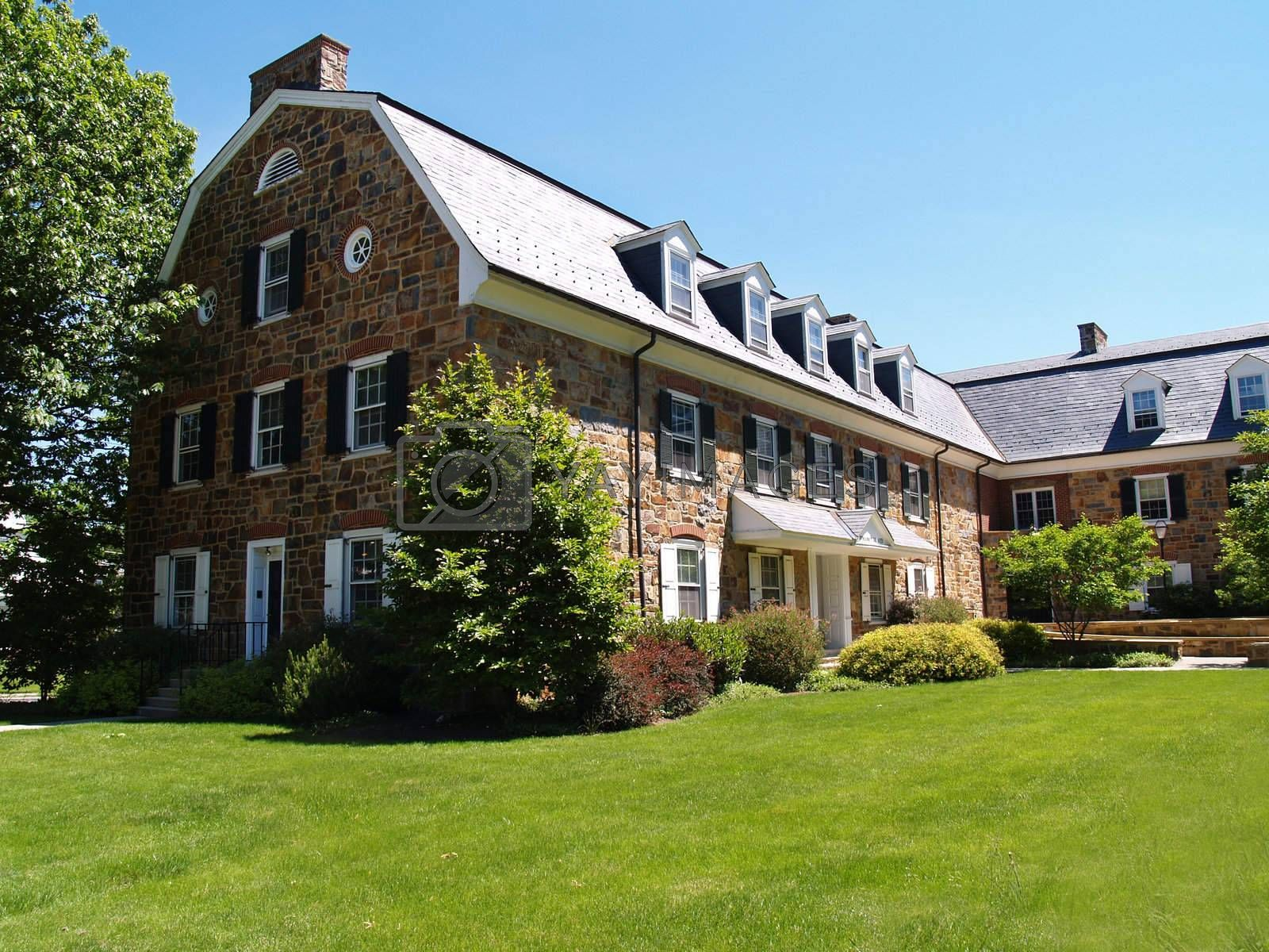 an old colonial style stone building with a gambrel roof